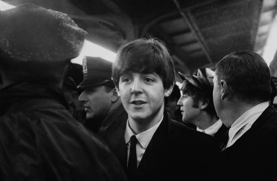 Paul McCartney and John Lennon are ushered through the crowd at Union Station on February 11, 1964. (Photo credit: Mike Mitchell)