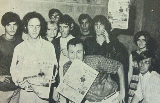 "WPGC deejay Jack Alix clenches a copy of GO Magazine between his teeth as he poses with ""The Doors,"" ""The Blades of Grass"" and the Jackettes Go-Go Girls at his ""Flower Power"" show in Alexandria, Virginia on August 18, 1967. The show was the only time that The Doors front man Jim Morrison is known to have returned to Alexandria, where he lived on and off during his childhood. (Photo source: Clinton, Maryland Star-Leader)"