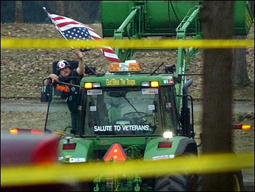 Dwight Watson on his tractor in pond at Constitution Gardens, 2003. (Photo source: Associated Press via Wikipedia)