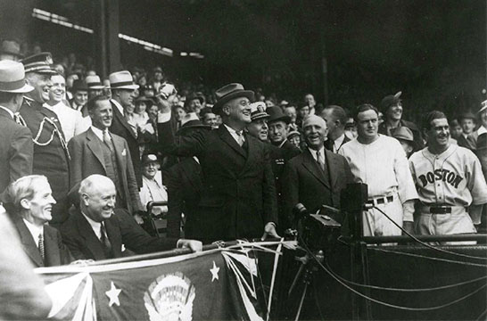 President Franklin D. Roosevelt, shown here in throwing out the ceremonial first pitch at Griffith Stadium in 1934, recommended that baseball continue during World War II. However, teams were expected curtail travel and conduct spring training close to home. (Photo source: National Archives)