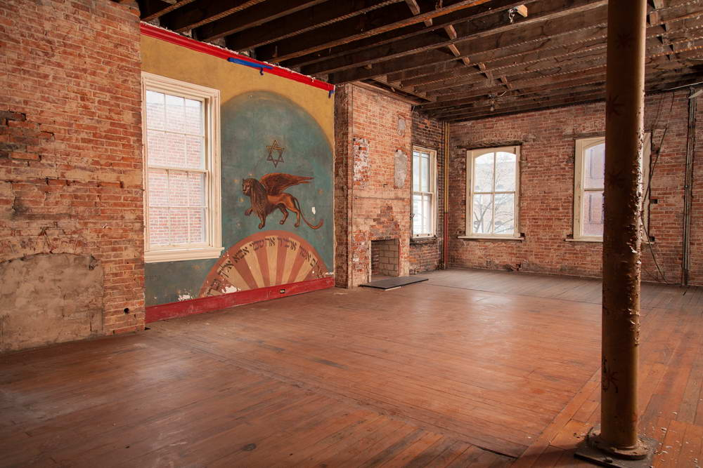 The mural is adjacent to a part of the floor that was removed to create a women's balcony when 415 M was a synagogue. Although the floor boards were subsequently replaced, the visible incongruity indicates the outline of the earlier hole between the first and second floors. Patricia Fisher, Fisher Photography, 2014.