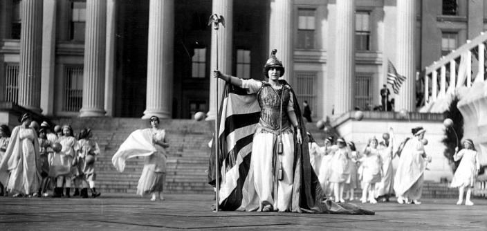 "German actress Hedwig Reicher wearing costume of ""Columbia"" with other suffrage pageant participants standing in background in front of the Treasury Building, March 3, 1913, Washington, D.C. (Source: Library of Congress)"