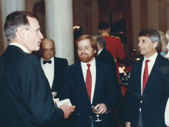 Jim Aidala and Bill Strauss standing with President George H.W. Bush in the White House.
