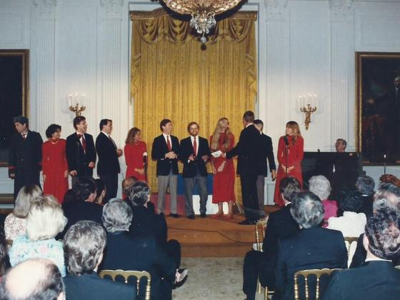 Seated audience in the foreground with the Capitol Steps and President H.W. Bush standing on stage in the White House in the background.