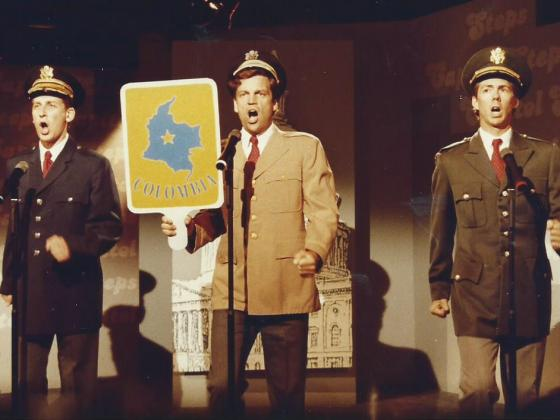 "Three men performing on stage at WETA with a sign that says ""Columbia""."