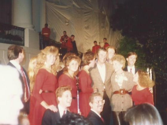 Capitol Steps performers standing with President Reagan and First Lady Nancy Reagan in front of the White House.