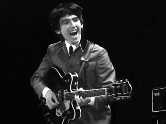 """George Harrison opened the show with a Chuck Berry cover, """"Roll Over Beethoven."""" Harrison was forced to switch mike stands as he sang the lead vocal, due to an apparent glitch in the sound system. (Photo credit: Mike Mitchell)"""