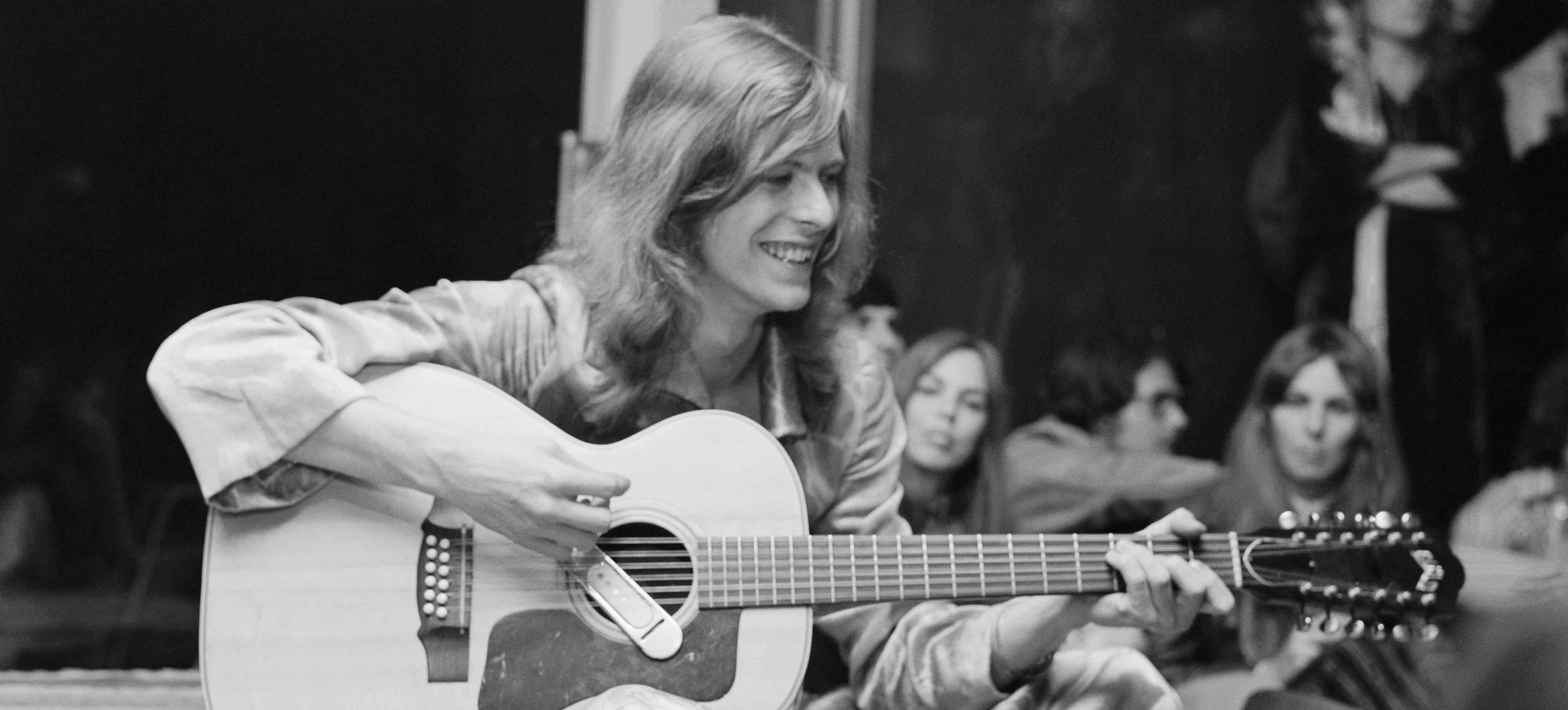 David Bowie jams at a party thrown by publicist Rodney Bingenheimer at lawyer Paul Figen's house in January 1971, in Los Angeles, California. (Photo by Earl Leaf/Michael Ochs Archives/Getty Images)