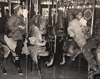 African American children enjoy cotton candy on the carousel after the desegregation of Glen Echo Park. (Photo source: National Park Service)