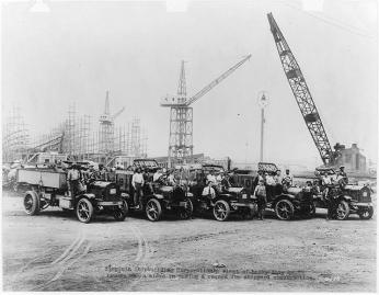 Five early 20th century trucks in the foreground with many men sitting in the front seats and a shipyard with cranes in the background