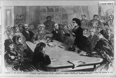 Victoria Woodhull speaks in front of the Judiciary Committee on January 11, 1871. This image is a drawing of a conference table with many suffragettes and congressmen surrounding it. Victoria Woodhull is standing and speaking. (Image Source: Library of Congress)