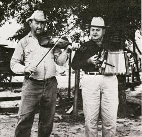 Two men standing in the foreground. The left person is playing a violin while the right person is playing an accordion.