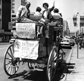 "William Porter and Helen Leavitt sit on the back of a stagecoach, showing a banner that reads, ""Taxation Without Representation."""
