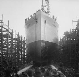 Back of peoples' heads in the foreground with a large boat in the background.